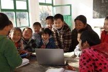 Insegnante donna rurale e alunni cinesi che utilizzano il computer portatile in classe — Foto stock