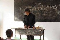 Maestro de escuela primaria rural chino masculino en el aula - foto de stock