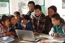 Insegnante donna rurale e alunni che utilizzano computer portatile insieme a scuola — Foto stock