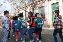 Китайские ученики начальной школы играют в игры на школьном дворе — стоковое фото