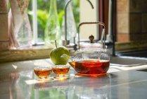 Vista ravvicinata del set da tè in vetro con bollitore e tazze di vetro sul tavolo — Foto stock