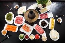 Vue élevée d'angle du hotpot de mouton avec les ingrédients délicieux sur la table — Photo de stock