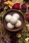 Top view of bowl with syrup and glutinous rice balls, dry flowers on table — Stock Photo
