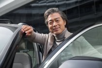 Mature asian man standing near car and smiling at camera — Stock Photo