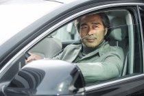 Smiling mature asian businessman driving car — Stock Photo