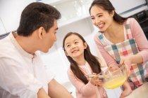 Счастливая семья с одним ребенком готовит вместе на кухне — стоковое фото
