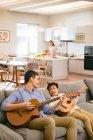 Blick aus der Vogelperspektive auf glückliche Väter und Söhne, die auf dem Sofa sitzen und Gitarre spielen, während die Mutter hinter der Küche kocht — Stockfoto