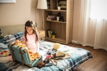 High angle view of adorable little asian girl packing suitcase on bed — Stock Photo