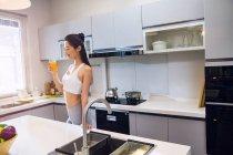 Sourire mince jeune femme tenant un verre de jus dans la cuisine — Photo de stock