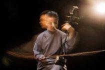 Человек играет на традиционном китайском национальном инструменте erhu — стоковое фото