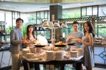 Cheerful young asian people standing at buffet and smiling at camera — Stock Photo