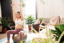 Sonriente joven embarazada sentada en la pelota de fitness y haciendo ejercicio con mancuernas en casa - foto de stock