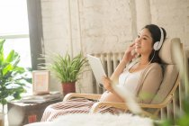 Smiling young pregnant woman in headphones sitting in rocking chair and using digital tablet at home — Stock Photo