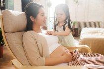Чарівна дитина з стетоскоп граючи з вагітною матір'ю в домашніх умовах — стокове фото
