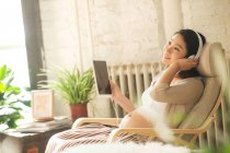 Happy young pregnant woman sitting in rocking chair with headphones and digital tablet — Stock Photo