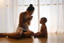 Счастливая молодая мать смотрит на восхитительного младенца в пеленках, сидящего на полу — стоковое фото