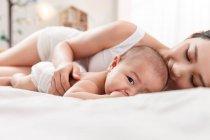 Молодая мама лежит на кровати с очаровательным младенцем, смотрящим в камеру — стоковое фото