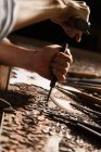Vista parziale in primo piano delle mani maschili durante l'incisione del legno in officina — Foto stock