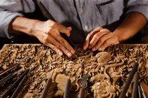 Coup recadré de mains masculines pendant la gravure de menuiserie, l'art et l'artisanat chinois traditionnels — Photo de stock