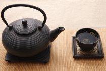 Черный керамический чайник и чашка чая на бамбуковом коврике — стоковое фото