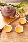 Vue d'angle élevé de théière brune et tasses sur le tapis en bambou — Photo de stock