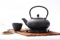 Черный керамический чайник и чашка чая на белом фоне — стоковое фото
