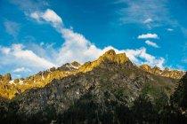 Incrível paisagem montanhosa com montanhas rochosas e nuvens brancas no céu azul — Fotografia de Stock