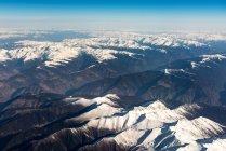 Vista aérea de belas montanhas cobertas de neve e céu azul — Fotografia de Stock