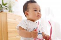 Lindo asiático bebé chico holding rosa gafas y mirando lejos - foto de stock