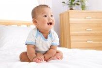 Lindo feliz asiático bebé chico sentado en cama y mirando lejos - foto de stock
