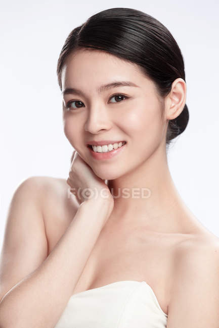 Portrait of elegant young asian woman smiling at camera isolated on grey — Stock Photo
