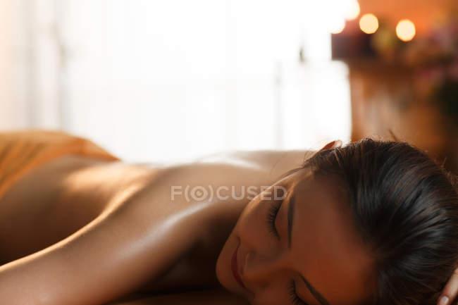 Vue rapprochée de attrayant sourire asiatique femme relaxant dans spa — Photo de stock