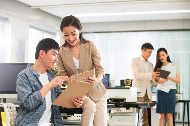 Young professional asian businesspeople working with clipboards and papers in office — Stock Photo