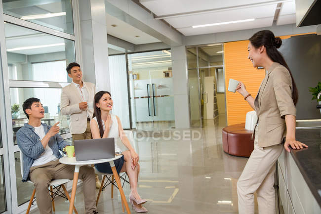 Side view of smiling young businesswoman holding cup of coffee and looking at colleorkers using laptop in office — стоковое фото