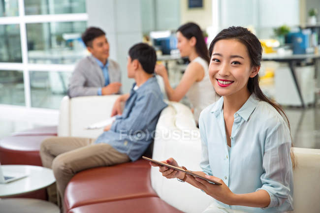 Beautiful happy young asian businesswoman holding digital tablet and smiling at camera in modern office — Stock Photo