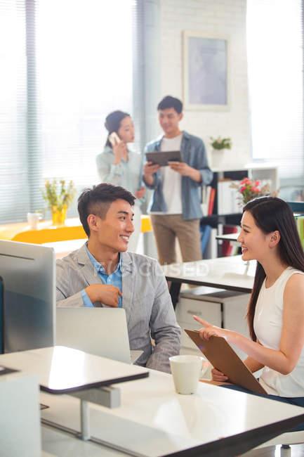 Jeune homme d'affaires heureux et femme d'affaires parlant et souriant mutuellement au lieu de travail, collègues travaillant derrière — Photo de stock