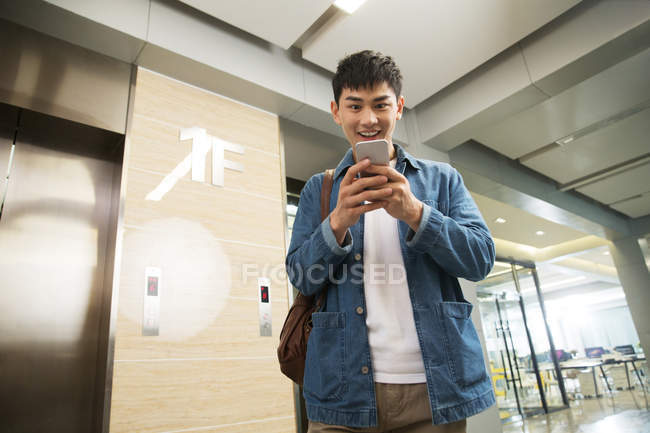 Low angle view of excited young businessman using smartphone in office — Stock Photo