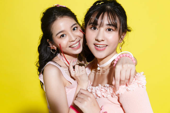 Beautiful happy asian girlfriends hugging and smiling at camera isolated on yellow — Stock Photo