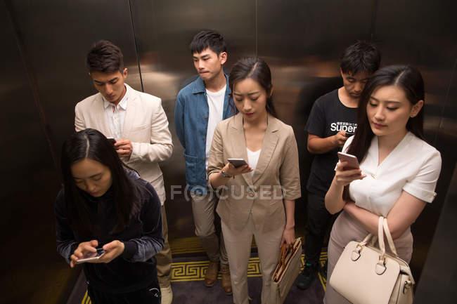 Vista ad alto angolo di giovani uomini e donne asiatici che utilizzano smartphone in ascensore — Foto stock