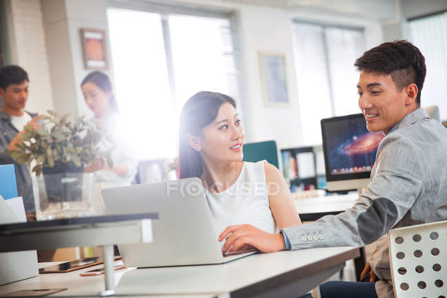Smiling young businessman looking at happy businesswoman using laptop at workplace — Stock Photo