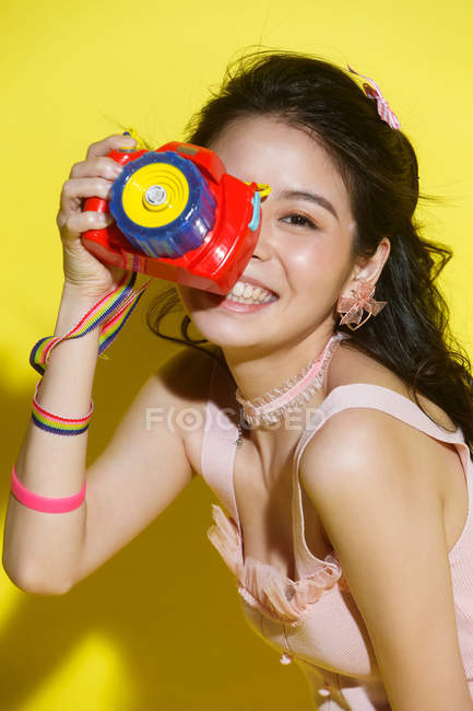 Beautiful happy young asian woman holding colorful camera and smiling on yellow — Stock Photo