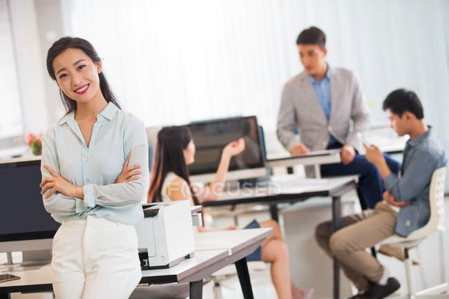 Beautiful young asian businesswoman with crossed arms smiling at camera while colleagues working behind in office — Stock Photo