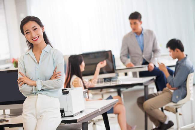 Bella giovane donna d'affari asiatica con le braccia incrociate sorridente alla fotocamera mentre i colleghi lavorano dietro in ufficio — Foto stock