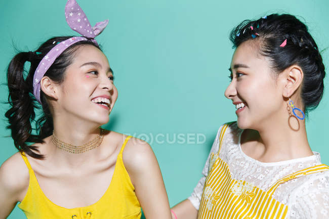 Beautiful happy stylish asian girls smiling each other on blue — Stock Photo