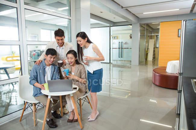 Heureux jeunes hommes d'affaires asiatiques et femmes d'affaires retenant des tasses et en utilisant l'ordinateur portable ensemble dans le Bureau — Photo de stock