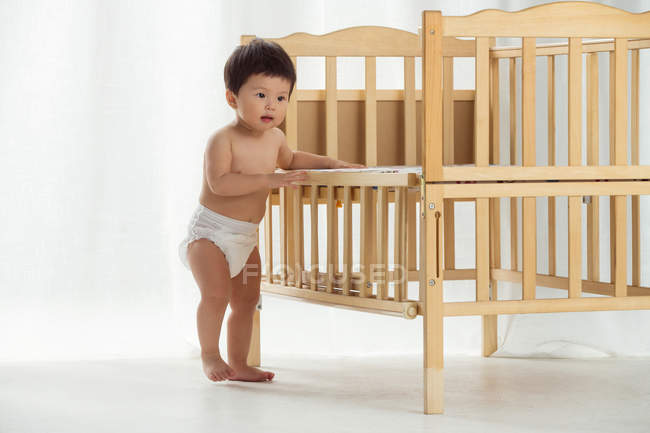 Full length view of adorable asian toddler in diaper leaning at crib and starting to walk at home — Stock Photo