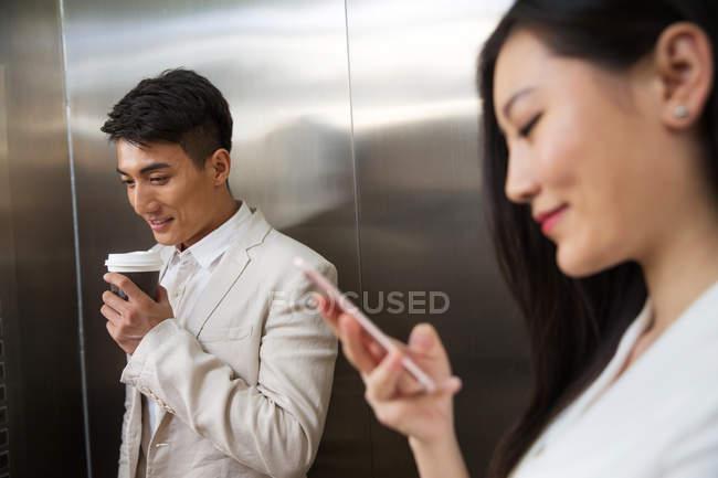 Молодой бизнесмен держит кофе идти и красивая деловая женщина с помощью смартфона на переднем плане в лифте — стоковое фото