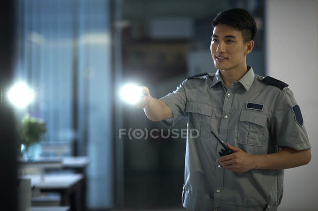 Smiling young security guard holding flashlight and walkie-talkie in office at night — Stock Photo