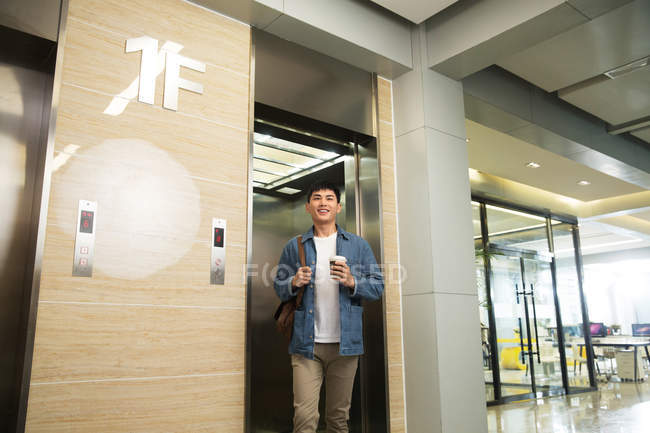 Low angle view of handsome happy young businessman holding coffee to go while walking from elevator in office — Stock Photo