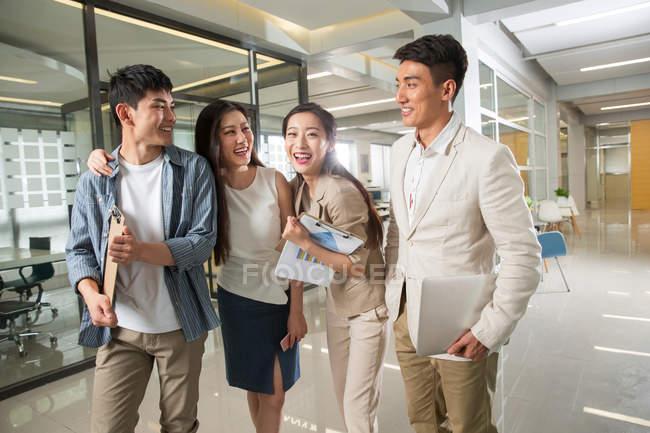 Счастливые молодые азиатские бизнесмены с ноутбуком, бумагами и буфером обмена ходить в офис — стоковое фото